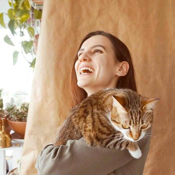 Retrato de Margalida Nadal, riendo con una gata color marron atigrada en sus brazos
